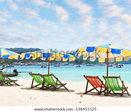 Wonderful vacation in the southern seas. Colorful beach umbrellas and deck chairs for leisure at the edge of the warm clear sea