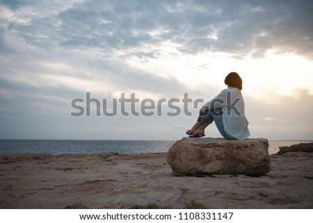 Wonderful view. Full length back view of thoughtful girl on beach is sitting on big round stone while enjoying sundown. She is looking at ocean and thinking dreamily. Copy space in the left side