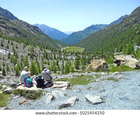 Wonderful view of a family with child having a good time and picnic in the mountain, on the Alps, Valle d'Aosta, Italy