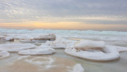 Wonderful view of the frozen sea coast in winter. Pieces of ice of different sizes. The sun behind the clouds, gives the sky interesting, unusual colors. Latvia. Baltic Sea.