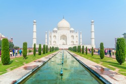Wonderful view of the Taj Mahal on blue sky background in Agra, India. The white marble mausoleum reflected in artificial pool. The Taj Mahal is a popular tourist attraction of South Asia.