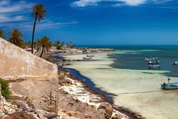 Wonderful views of the Mediterranean coast with birch water, white sand beach and a fishing boat.