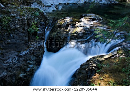Wonderful waterfall in long exposure mode is featured in this nature photograph, featuring the silky looking water cascading over the edges, surrounded by a rocky riverbed and forest trees.