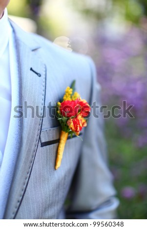 Wonderful wedding boutonniere on a costume of groom from beautiful colorful flowers. Nice bokeh in the background.