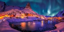 Wonderful winter scenery. popular touristic destination Reine. colorful night scene with Green northern lights above mountains Lofoten Islands. One of the most wonderfull nature sightseeing in Norway.