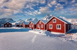 Wonderful winter view on snowcapped mountains, red fishing huts and cloudy sky. Typical nature landscape of Lofoten islands. Norway. Travel, adventure and freedom concept. popular travel destinations