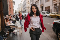 Wonderful young woman in formal attire walking down the street. Elegant brunette lady in glasses enjoying city views in morning.