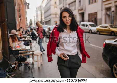 Wonderful young woman in formal attire walking down the street. Elegant brunette lady in glasses enjoying city views in morning. ストックフォト ©
