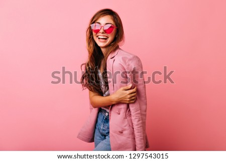 Wonderful young woman with long hair having fun on rosy background. Magnificent girl in trendy sunglasses relaxing during photoshoot.