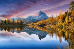 Wonderfull autumn view of  Lake Federa in Dolomites  at sunset. Fantastic autumn scene with colour sky, colorful trees glowing sunlight in Dolomites. Location: Federa lake with Dolomites peak, Cortina