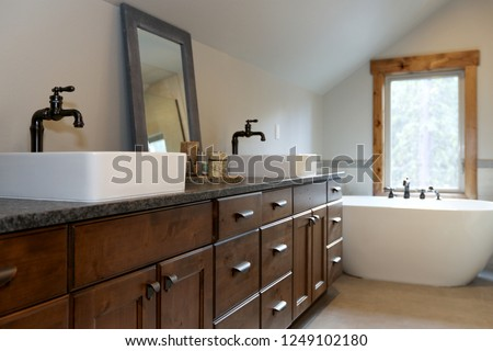 Wonderfully designed bathroom in a country house boasts dual washstand with dark granite countertop and rectangular vessel sinks. #1249102180