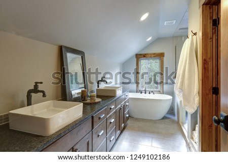 Wonderfully designed bathroom in a country house boasts dual washstand with dark granite countertop and rectangular vessel sinks. #1249102186