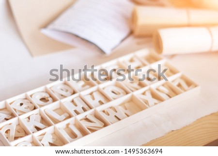 Wood alphabet in box on table in warm light