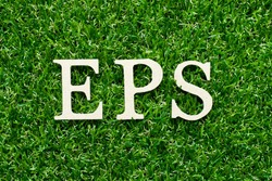Wood alphabet letter in word EPS (Abbreviation of Earnings per share) on green grass background