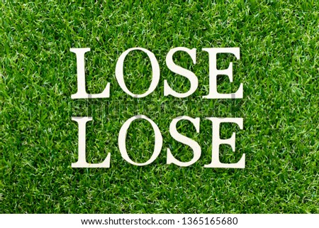 Wood alphabet letter in word lose lose on green grass background