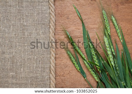 Wood and canvas textures with green wheat background