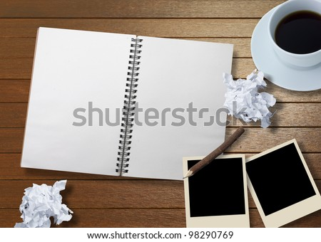 wood background with notebook and photo frame
