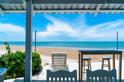wood bar and chair with ocean sea beach and blue sky background
