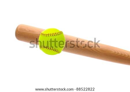 Wood bat hitting a yellow softball over a white background.
