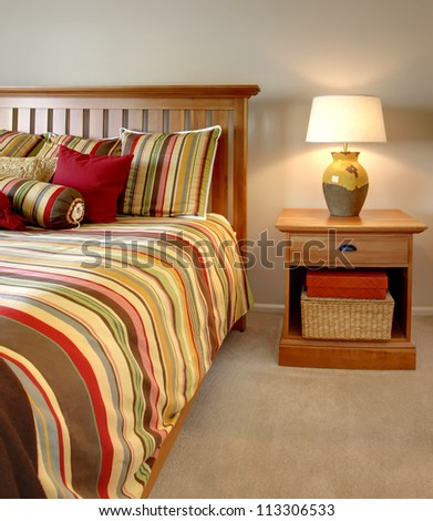 Wood bed and nightstand with stripes in red, yellow and green with beige carpet.