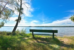 Wood bench on a beach of Volga river and pine forest on another side in sunny and cloudy day.