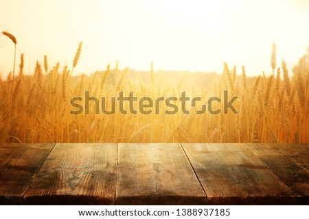 wood board table in front of field of wheat on sunset light. Ready for product display montage Stock photo ©