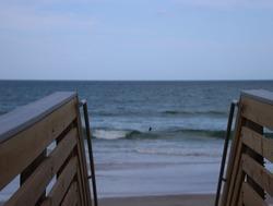 Wood boardwalk walkway access to beach on sunny blue sky day.