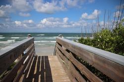 Wood boardwalk walkway to beach on sunny blue sky day.