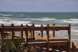 Wood boardwalk walkway to beach on sunny  day.