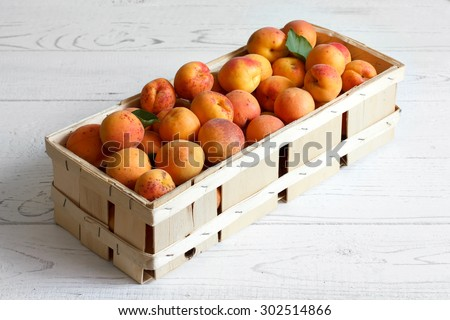 Wood box of whole orange apricots with red blush on rustic white wood. Space for text.