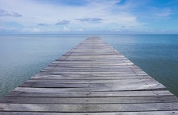 Wood bridge of walk way for travel on the sea with blue sky,Thailand.