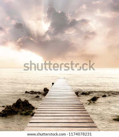 Wood bridge on the sea which has walk way for travel with beautiful sky and sunshine background.