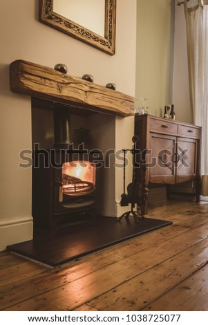 Wood burning stove fireplace with oak mantelpiece and wooden floorboards