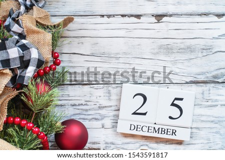 Wood calendar blocks with the date December 25th to mark Christmas Day with ornaments, black and white buffalo check and red bead garland over white rustic table background. Top view with copy space.