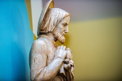Wood carved Jesus statue blu wall and yellow wall