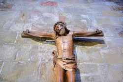 wood carving of Christ crucified on stone wall in Leyre Monastery