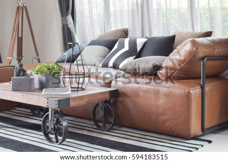 Wood center table with wheel and light brown leather sofa in industrial style decoration