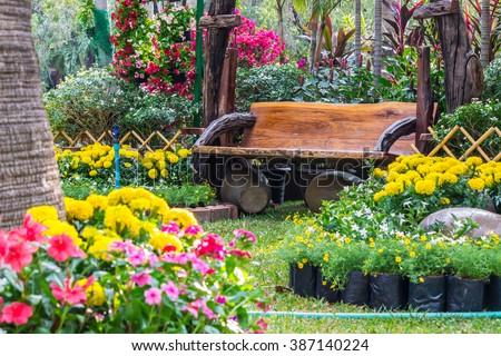 Wood chair in the flowers garden./ Flowers in the garden.