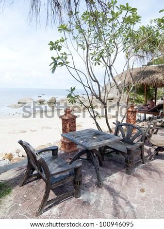 wood chairs on tropical beach