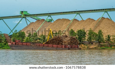 wood chip stockpile / factory on Mahakam riverbank. industrial background #1067578838