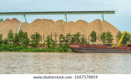 wood chip stockpile factory on Mahakam riverbank. industrial background #1067578859