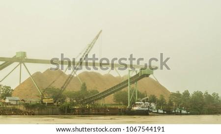 wood chip stockpile on Mahakam riverbank in a misty morning, Borneo, Indonesia #1067544191