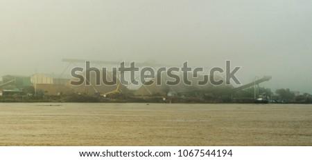 wood chip stockpile on Mahakam riverbank in a misty morning, Borneo, Indonesia #1067544194