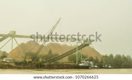 wood chip stockpile on Mahakm riverbank, Borneo, Indonesia on misty morning #1070266625