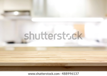Wood countertop (or kitchen island) on blur kitchen interior background - can be used for display or montage your products