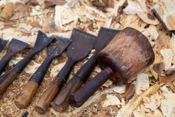 Wood craftsmanship carve tools. Chisel with wood shavings. Carpenter cabinet maker hand tools on the workbench.