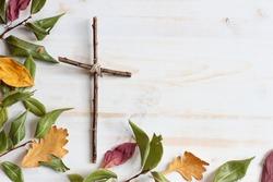 Wood cross with autumn leaf border on white wood background