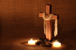 Wood cross with cloth by candles and stones and rustic background; Easter, Christmas, Memorial Day, and religious background with copy space