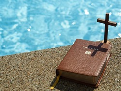 Wood Crucifix  and bible in sunlight with blue water bokeh as background. Christianity, study bible, God word concept.