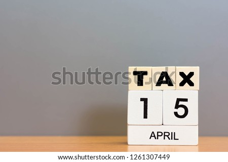 Wood cube tax and coin money stack on wooden table background.  The deadline to pay taxes. Tax Day 2019 takes place on April 15 copy space